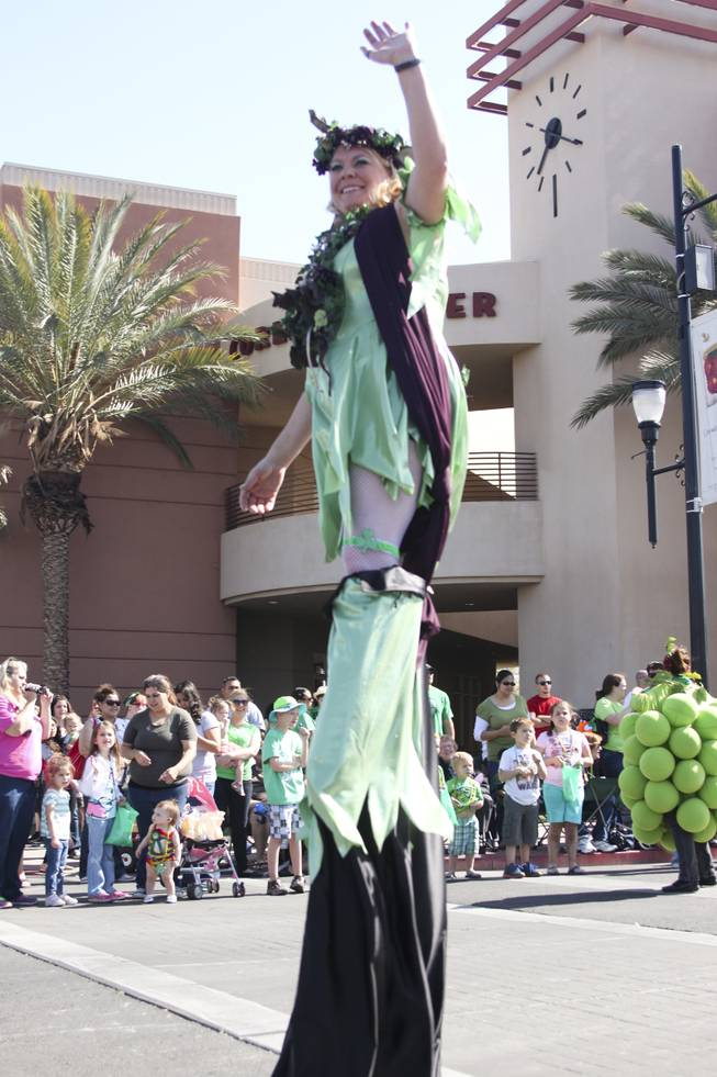 A participant on stilts waves to the crowd during the annual St. Patrick's Day parade in Henderson Saturday, March 15, 2014.