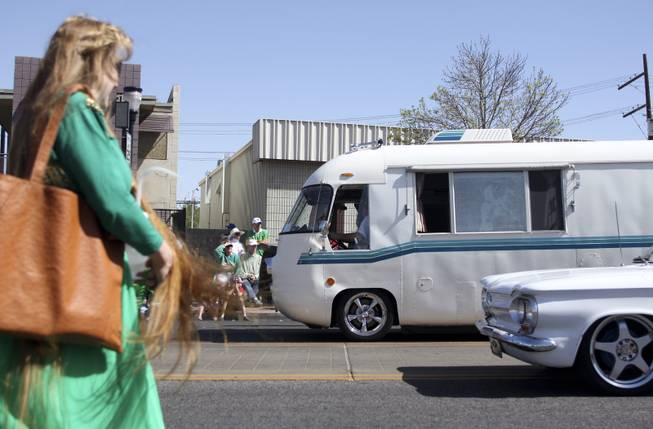 A woman walks past as the antique vehicles from the High Roller Las Vegas club drive by during the annual St. Patrick's Day parade in Henderson Saturday, March 15, 2014.