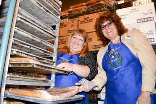Misti Gower, left, and Heidi Englund check the cakes that will be used to make the state's 150th anniversary cake. It will measure 21 feet long by 13 feet wide and be in the shape of the state.