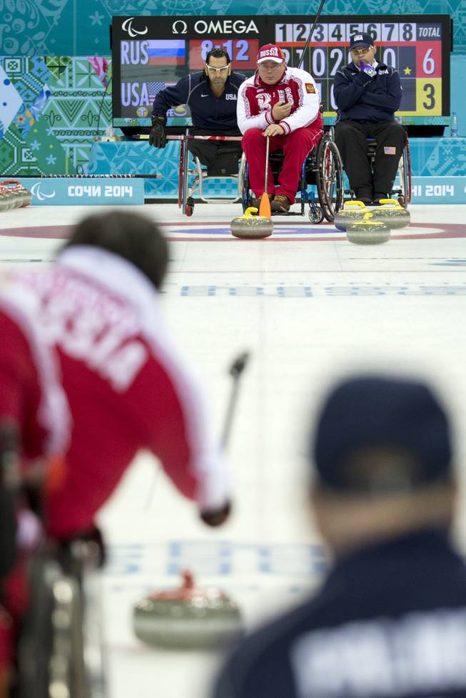 Russia's Andrey Smirnov, top center, lines up a shot during wheelchair curling match between United States and Russia at the 2014 Winter Paralympics in Sochi, Russia, Monday, March 10, 2014. Russia won 6-5.
