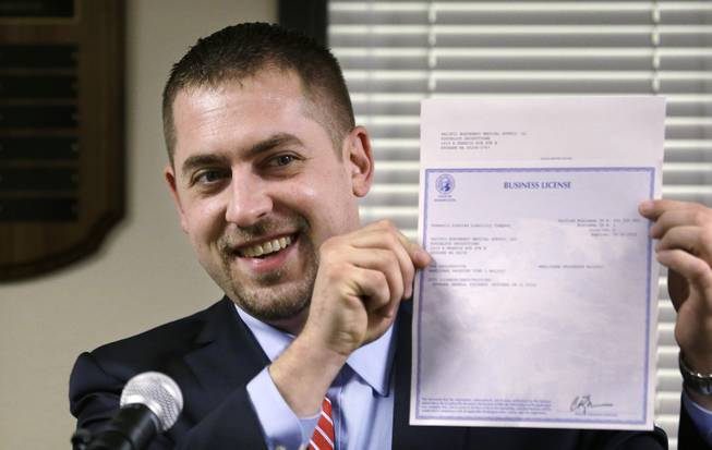 In this March 5, 2014, file photo, Sean Green displays his newly-issued Washington state legal marijuana license in Olympia, Wash.