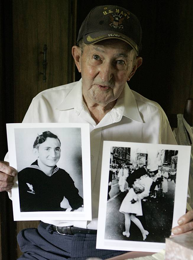 In this July 31, 2007, file photo, Glenn McDuffie holds a portrait of himself as a young man, left, and a copy of Alfred Eisenstaedt's iconic Life magazine shot of a sailor, who McDuffie claims is him, embracing a nurse in a white uniform in New York's Times Square, at his Houston home.