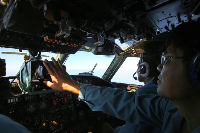 A cabin crew of the Vietnam air force is seen onboard a flying AN-26 Soviet-made aircraft during a search operation for the missing Malaysia Airlines flight MH370 plane over the southern sea between Vietnam and Malaysia Friday, March 14, 2014.