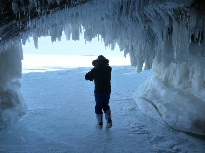 Patti Heil visits caves covered in ice along Lake Superior near Cornucopia, Minn. A deep freeze this winter has made it so people can walk across the frozen lake and look at the natural ice formations, but it has also hindered shipping in the region.