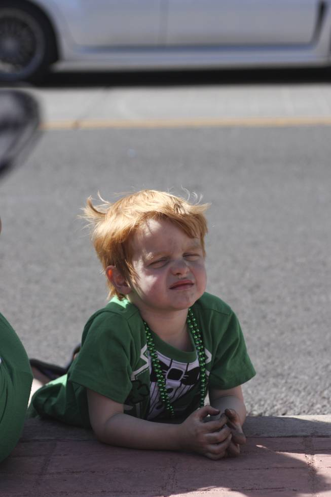 A little boy lays on the side walk looking on to the crowd towards the end of the annual St. Patrick's Day parade in Henderson Saturday, March 15, 2014.