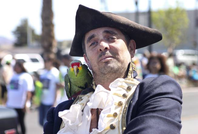 A member from the Pirate Fest group poses with his parrot for the camera during the annual St. Patrick's Day parade in Henderson Saturday, March 15, 2014.