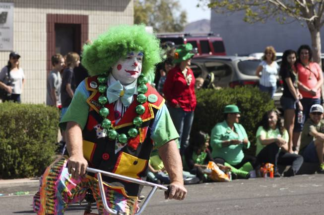 A member of the Zelzah Shrine Clowns ride by on his bike during the annual St. Patrick's Day parade in Henderson Saturday, March 15, 2014.