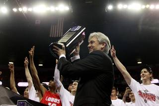 New Mexico coach Craig Neal hoists their trophy after defeating San Diego State 64-58 in their Mountain West Conference tournament championship game Saturday, March 15, 2014 at the Thomas & Mack Center.