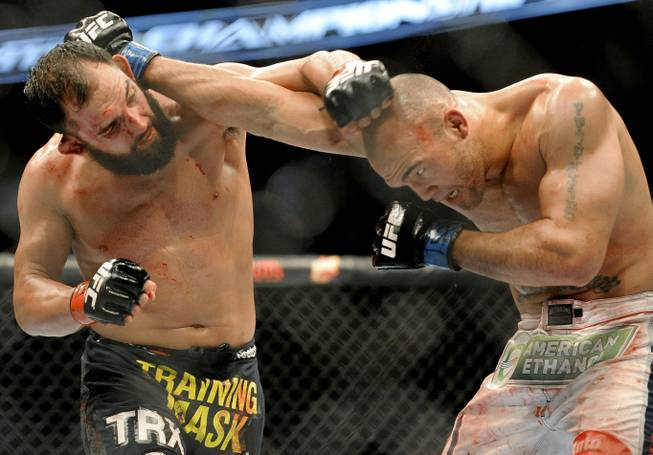 Johny Hendricks, left, and Robbie Lawler exchange punches during a UFC 171 mixed martial arts welterweight title bout, Saturday, March 15, 2014, in Dallas. Hendricks won by decision.