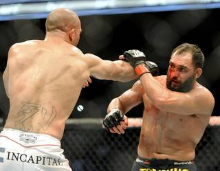 Johny Hendricks blocks a punch from Robbie Lawler during a UFC 171 mixed martial arts welterweight title bout, Saturday, March 15, 2014, in Dallas. Hendricks won by decision.