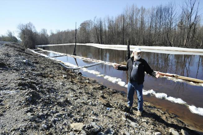 John Wathen, an environmentalist with the Waterkeeper Alliance, gestures at the site of a train derailment and oil spill near Aliceville, Ala., on Wednesday, May 5, 2014. Environmental regulators say cleanup and containment work is continuing at the site, but critics contend the accident and others show the danger of transporting large amounts of oil in tanker trains.