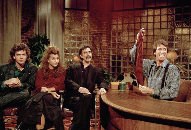 "In this Sept. 24, 1986, file photo, comedian David Brenner hosts avant garde fusion musician Frank Zappa, center, and his children, Dweezil, left, and Moon Unit, during a taping of Brenner's ""Nightlife"" talk show in New York. Brenner holds a necktie given to Frank Zappa upon entering a restaurant earlier in the day. Brenner has died at the age of 78."