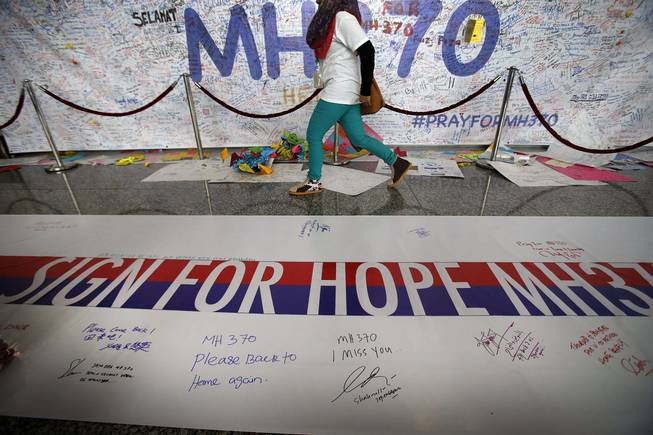 A woman walks past a banner filled with signatures and well-wishes for all involved with the missing Malaysia Airlines jetliner MH370 at the Kuala Lumpur International Airport, Sunday, March 16, 2014 in Sepang, Malaysia. Malaysian authorities Sunday were investigating the pilots of the missing jetliner after it was established that whoever flew off with the Boeing 777 had intimate knowledge of the cockpit and knew how to avoid detection when navigating around Asia.