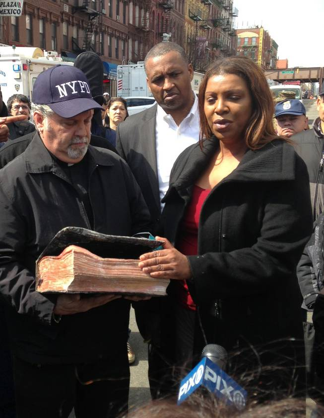Rick Del Rio, pastor of Abounding Grace church in Manhattan, and New York City Public Advocate Letitia James, display a damaged but intact Bible they said was recovered in the rubble of the Spanish Christian Church, Saturday, March 15, 2014 in New York. The church was in one of the buildings destroyed in the March 12 gas explosion that leveled two building and killed eight people.