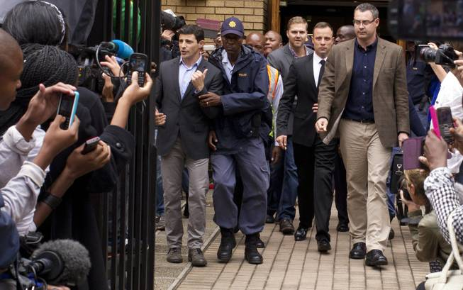 Oscar Pistorius, center, walks out of the high court in Pretoria, South Africa, on Friday, March 14, 2014. Pistorius is charged with murder for the shooting death of his girlfriend, Reeva Steenkamp, on Valentine's Day 2013.
