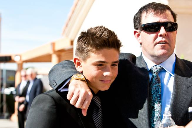 "Grandsons Brendan and John Gaughan, left, share an embrace will attending the memorial mass for their grandfather, John Davis ""Jackie"" Gaughan, held at St. Viator Catholic Church in Las Vegas on St. Patrick's Day, March 17, 2014."