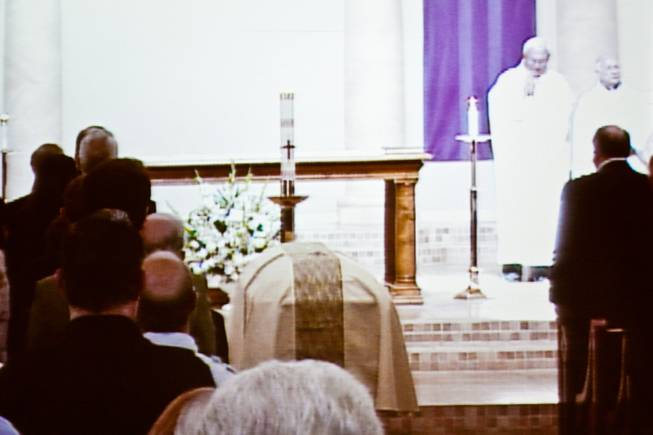 "As seen on an overflow video monitor, the casket of John Davis ""Jackie"" Gaughan lies in wait during the memorial mass at St. Viator Catholic Church in Las Vegas on St. Patrick's Day, March 17, 2014.  Jackie Gaughan, 93, passed away March 12, 2014."