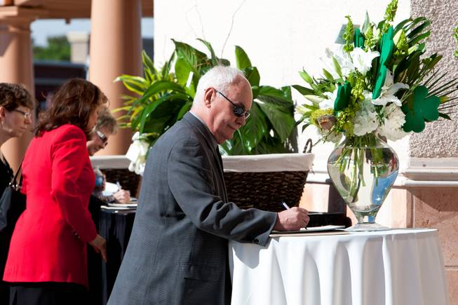 "Surrounded by green floral arrangements and shamrocks, Steven Green signs a guestbook while attending the memorial mass for John Davis ""Jackie"" Gaughan held at St. Viator Catholic Church in Las Vegas on St. Patrick's Day, March 17, 2014."