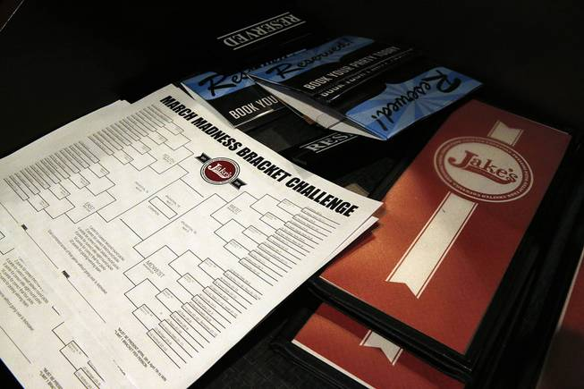 A stack of blank NCAA brackets sits with menus, available to patrons at Jake's sports bar, in Denver, Monday, March 17, 2014.