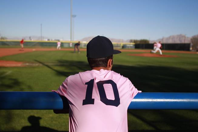 A Canyon Springs player watches from the dugout  during their game against Western Wednesday, March 19, 2014. The Pioneers wore pink jerseys for the game for cancer awareness and to honor parents of two of the players who died from cancer in the past year.