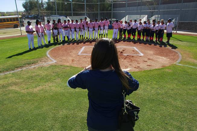 Kelly Webb from the Candlelighters takes a photo of the Canyon Springs baseball and softball teams before  their game against Western Wednesday, March 19, 2014. The Pioneers wore pink jerseys for the game for cancer awareness and to honor parents of two of the players who died from cancer in the past year.