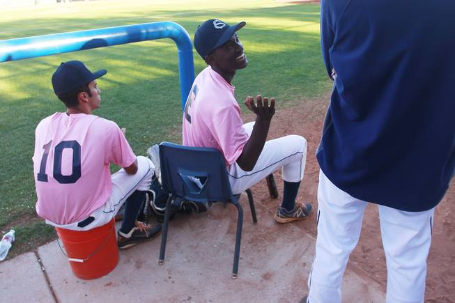 Canyon Springs outfielder Rashaad Jones jokes with a coach during their game against Western Wednesday, March 19, 2014. The Pioneers wore pink jerseys for the game for cancer awareness and to honor parents of two of the players who died from cancer in the past year.