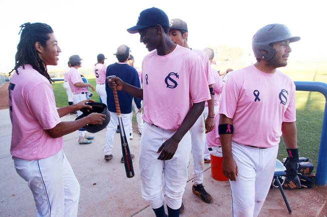 Canyon Springs outfielder Rashaad Jones hands his bat to a teammate during their game against Western Wednesday, March 19, 2014. The Pioneers wore pink jerseys for the game for cancer awareness and to honor parents of two of the players who died from cancer in the past year.