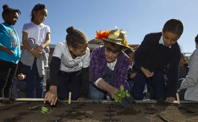 Student Azia La Rue, 9, Judith Allan and Shakur Ahmed, 9, join others from Joseph E. Thiriot Elementary School and the Create A Change Now organization to plant an edible garden on Wednesday, March 19, 2014.