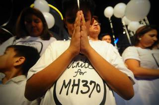 A young Malaysian boy prays, at an event for the missing Malaysia Airline, MH370, at a shopping mall, in Petaling Jaya,  on the outskirts of Kuala Lumpur, Malaysia, Tuesday, March 18, 2014.