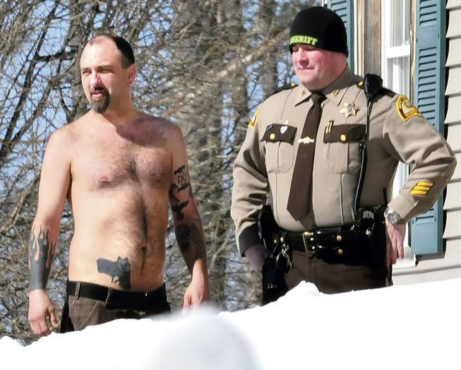 In this Tuesday, March 18, 2014, photo, Michael Smith, left, stands beside a Somerset County Sheriff deputy outside his home in Norridgewock, Maine.