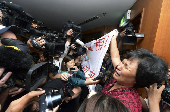 "A Chinese relative of passengers aboard a missing Malaysia Airlines plane cries as she holds a banner in front of journalists reading 'We are against the Malaysian government for hiding the truth and delaying the rescue. Release our families unconditionally!"" at a hotel in Sepang, Malaysia, Wednesday, March 19, 2014."