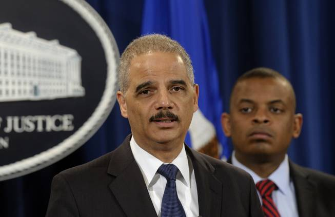 Attorney General Eric Holder, left, accompanied by Transportation Secretary Anthony Foxx, announces a $1.2 billion settlement with Toyota over its disclosure of safety problems, Wednesday, March 19, 2014, during a news conference at the Justice Department in Washington.