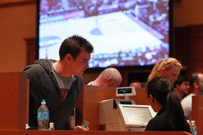 Bettors make their wagers in a ballroom during the second round of the NCAA basketball tournament Thursday, March 20, 2014, at South Point.
