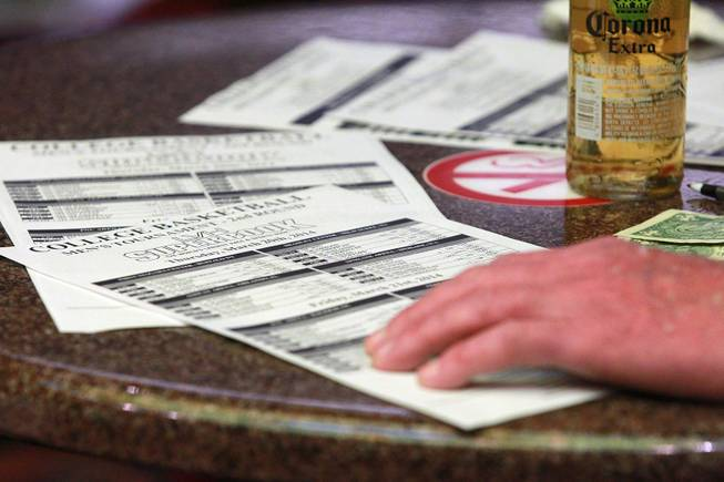 A bettor and his odds sheets at the LVH sports book during the second round of the NCAA basketball tournament Thursday, March 20, 2014.