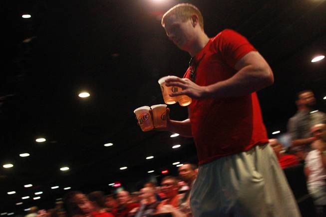 A patron carries beer back to his seat in the theater of the LVH during the second round of the NCAA basketball tournament Thursday, March 20, 2014.