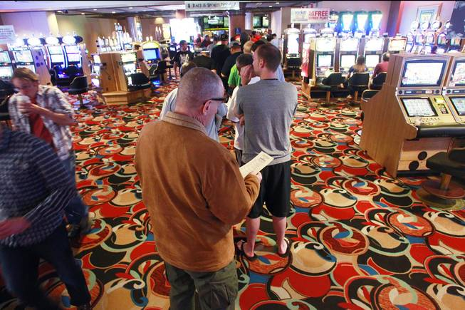Bettors stand in line to make their wagers at the LVH sports book during the second round of the NCAA basketball tournament Thursday, March 20, 2014.