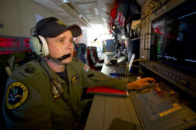 In this Wednesday, March 19, 2014, photo released by the Australia Defense Department, Royal Australian Air Force airborne electronics analyst Flight Sgt. Tom Stewart, on board an AP-3C Orion, watches a radar screen over the Southern Indian Ocean during a search operation for missing Malaysia Airlines flight MH370.