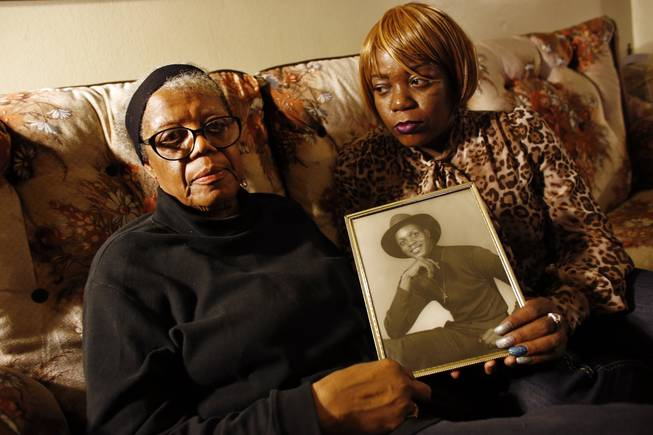 In this March 12, 2014, photo, Alma Murdough and her daughter Cheryl Warner hold a photo of Murdough's son at her home in the Queens borough of New York. Jerome Murdough, a mentally ill, homeless former Marine arrested for sleeping in the roof landing of a New York City public housing project died last month in a Rikers Island jail cell that multiple city officials say was at least 100 degrees when his body was discovered.