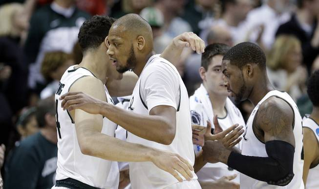 Michigan State's Adreian Payne, center, and Branden Dawson, right, are greeted with hugs as they head to the bench in the final moments of the second half during the second round of the NCAA men's college basketball tournament against Delaware in Spokane, Wash., Thursday, March 20, 2014. Michigan State won 93-78.