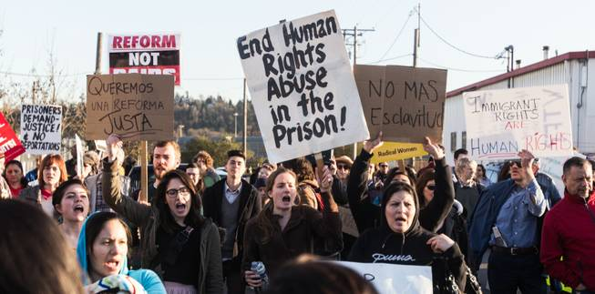 Demonstrators opposing deportations hold up signs while chanting in English and Spanish outside of the Northwest Detention Center in Tacoma, Wash. Tuesday, March 11, 2014.