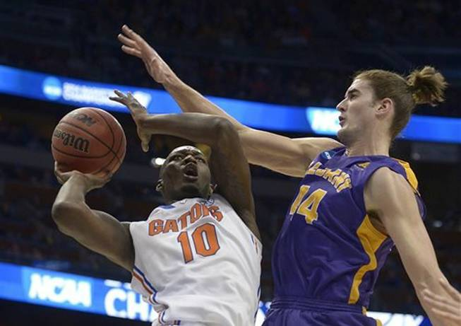 Albany center John Puk (44) fouls Florida forward Dorian Finney-Smith (10) during the first half of a second-round game in the NCAA college basketball tournament on Thursday, March 20, 2014, in Orlando, Fla.