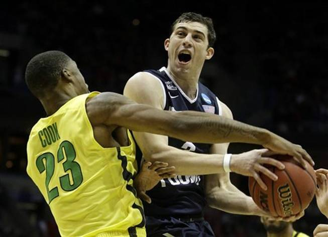 BYU guard Matt Carlino is fouled by Oregon forward Elgin Cook (23) during the first half of a second-round game in the NCAA college basketball tournament Thursday, March 20, 2014, in Milwaukee.