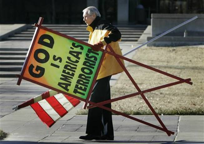 In this July 1, 2007, file photo, the Rev. Fred Phelps Sr. prepares to protest outside the Kansas Statehouse in Topeka, Kan. Phelps, the founder of the Kansas church known for anti-gay protests and pickets at military funerals, died Thursday, March 20, 2014. He was 84.