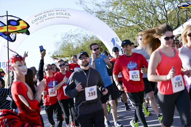 Participants cross the starting line at the onset of the Run Away with Cirque du Soleil 5K Run and One-Mile Fun Walk at the Springs Preserve on Saturday, March 15, 2014.