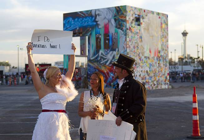 Betsy Donat (L) and Christian Ardita exchange wedding vows before the burning of the Life Cube (background), an interactive community art installation, in downtown Las Vegas, Friday March 21, 2014. Donna Manto looks on at center. The Life Cube, a creation of artist Scott Cohen, was a 24-by-24-foot plywood cube, painted by artists and filled with notes from thousands of people.