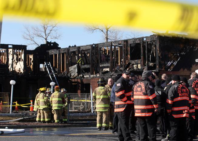 Firefighters investigate a fatal fire at the Mariner's Cove Hotel in Point Pleasant Beach, N.J. on Friday, March 21, 2014.