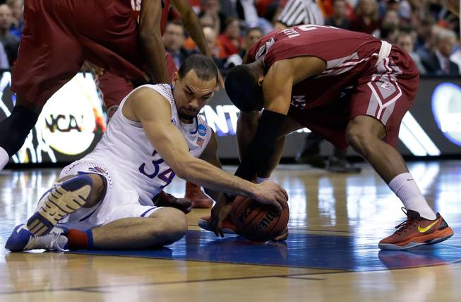 Kansas' Perry Ellis, left, and Eastern Kentucky's Corey Walden fight over a loose ball during the first half of a second-round game in the NCAA college basketball tournament Friday, March 21, 2014, in St. Louis.