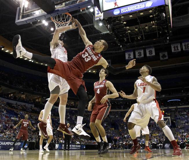 New Mexico's Cameron Bairstow, left, blocks a shot by Stanford's Dwight Powell (33) during the first half of a second-round game in the NCAA college basketball tournament, Friday, March 21, 2014, in St. Louis.