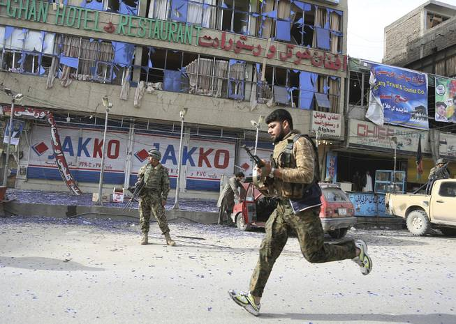 Afghan police officers arrive to the scene after a multi-pronged attack on a police station in Jalalabad, the capital of eastern Nangarhar province, Afghanistan, Thursday, March 20, 2014.