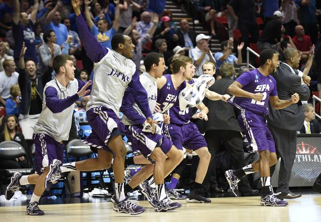 Stephen F. Austin players run onto the court as they beat Virginia Commonwealth 77-75 in overtime in a second-round game in the NCAA college basketball tournament Friday, March 21, 2014, in San Diego.